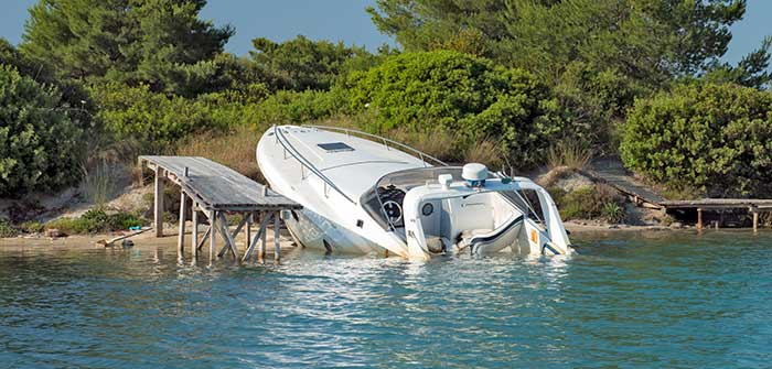 Speedboat-beached-and-partially-sunk-at-its-mooring